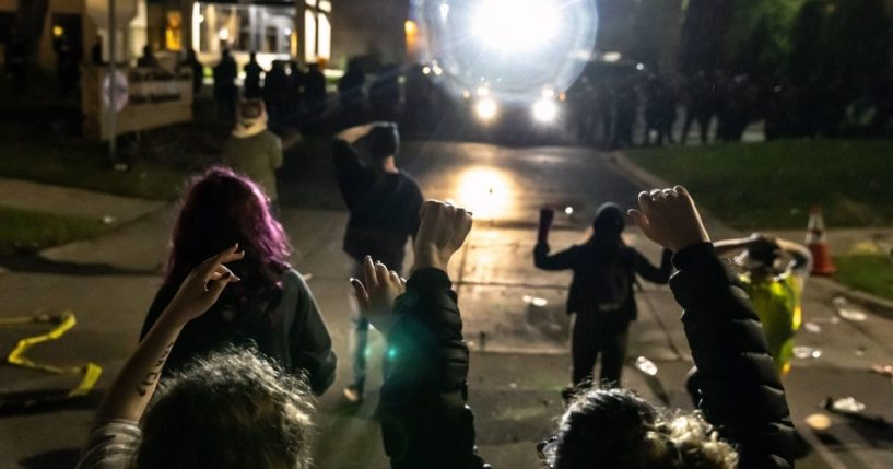 Protesters face off against a line of police officers at the Brooklyn Center Police Station in Minneapolis on April 11, 2021.