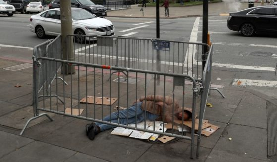A homeless man sleeps on the sidewalk near San Francisco City Hall on Dec. 5, 2019, in San Francisco.