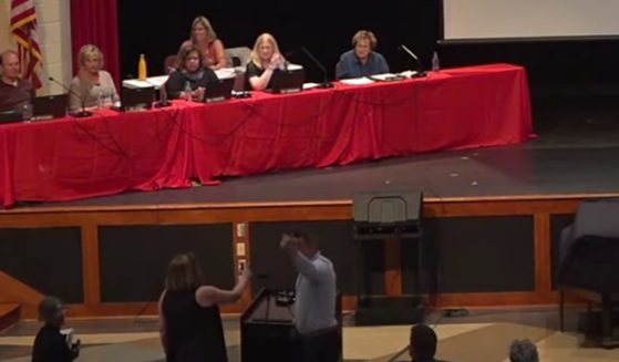 Anita Edgarian, bottom left, speaks with local school board president Chris McCune, bottom right, at a meeting on July 26, 2021, in West Chester, Pennsylvania.