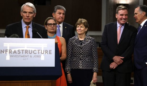 Sen. Rob Portman of Ohio speaks alongside, left to right, Sens. Kyrsten Sinema of Arizona, Joe Manchin of West Virginia, Jeanne Shaheen of New Hampshire, Mark Warner of Virginia and Mitt Romney during a news conference on the bipartisan infrastructure package at the Dirksen Senate Office Building on Capitol Hill in Washington on July 28.