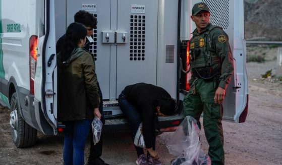A Border Patrol agent processes a group of migrants in Sunland Park, New Mexico, on July 22, 2021.
