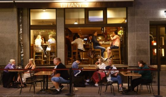 People sit at tables outside a restaurant in Stockholm as COVID restrictions for opening hours at restaurants and bars have been removed completely on July 1, 2021.