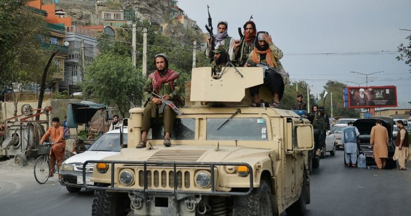 Taliban fighters atop a Humvee take part in a rally in Kabul on Tuesday.