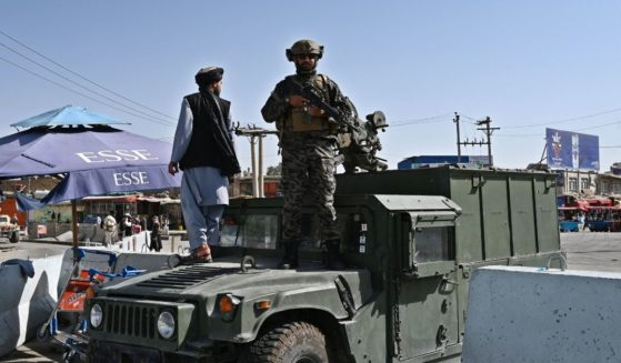 A Taliban fighter stands guard on a Humvee at the main entrance gate of the Kabul airport on Saturday in Afghanistan.