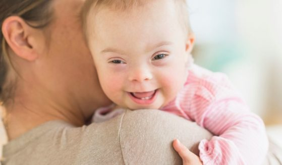 In this stock photo, a woman is seen holding a baby with Down syndrome. Pro-abortion groups filed a lawsuit Tuesday seeking to overturn a new Arizona law that would ban abortions because of Down syndrome or other genetic abnormalities. (