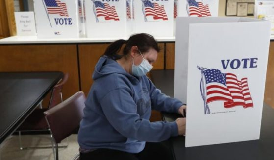 A woman wearing a mask is seen filling out an absentee ballot at City Hall in Garden City, Michigan.