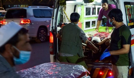 Medical staff bring an injured man to a hospital in an ambulance after two powerful explosions, which killed at least six people, outside the airport in Kabul on Thursday.
