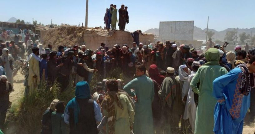 Taliban fighters and Afghans are seen gathered around a body in the city of Farah in southwest Afghanistan on Wednesday.