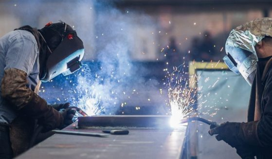 Workers welding in a factory.