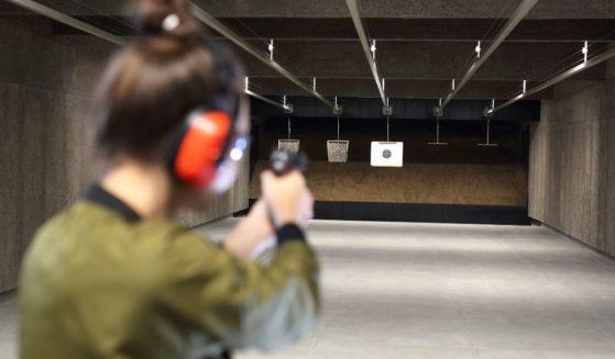 A woman shoots a handgun at a target at a gun range.