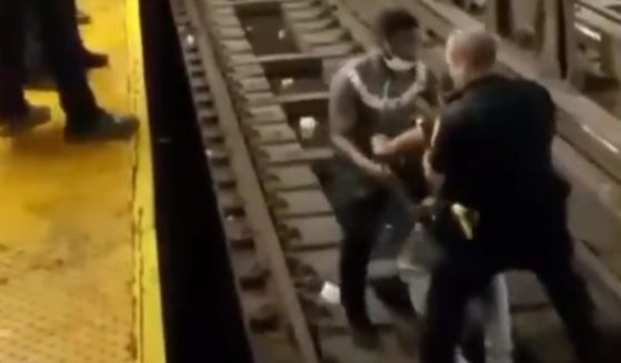 An NYPD officer and a Good Samaritan pick up an ill man from a subway track in New York City before carrying him to safety on Aug. 19, 2021.