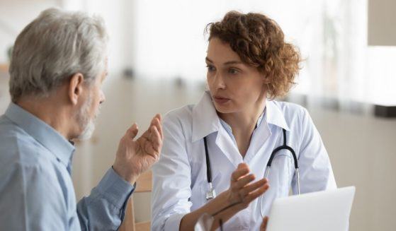 A female doctor consulting with an elderly male patient.