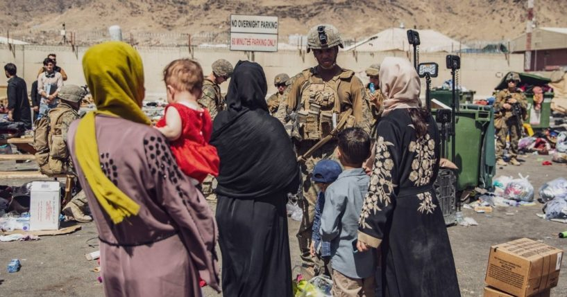 In an image provided by the U.S. Marine Corps, Marines process evacuees Hamid Karzai International Airport in Kabul, Afghanistan, on Saturday.