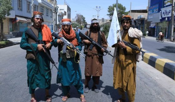 Taliban fighters are seen standing in a road in Herat, Afghanistan, on Thursday.