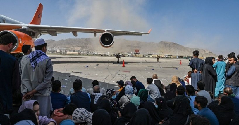 A crowd of Afghan people is seen sitting at the airport in Kabul in Afghanistan on Monday.