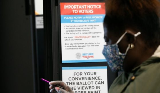 A female voter is seen casting a ballot in a voting booth in Atlanta, Georgia, on Nov. 3, 2020.