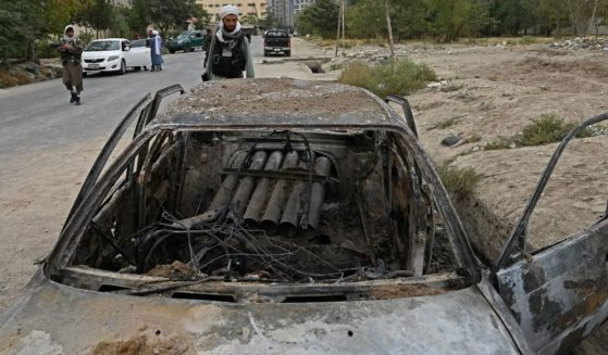 A Taliban fighter investigates a damaged car Monday after multiple rockets were fired in Kabul.
