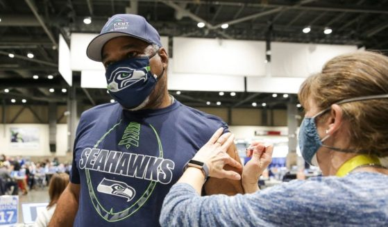 Cleveland Hughes wears Seahawks gear as he gets the Pfizer COVID-19 vaccine from Andrea Barnett at the Lumen Field Event Center in Seattle on March 13, 2021.