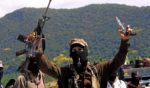Masked Zapatista Subcommander Marcos smokes a pipe and displays weapons Feb. 24, 2001, in La Realidad, Mexico.