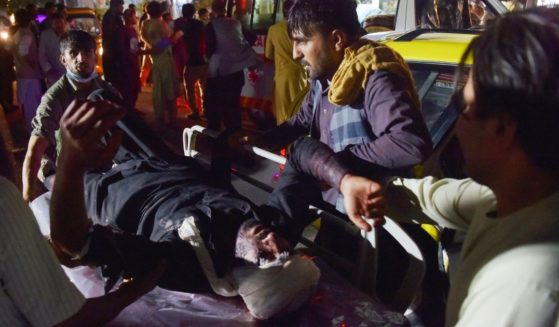 Medical and hospital staff bring an injured man on a stretcher for treatment after two blasts, which killed at least five and wounded a dozen, outside the airport in Kabul on Thursday.