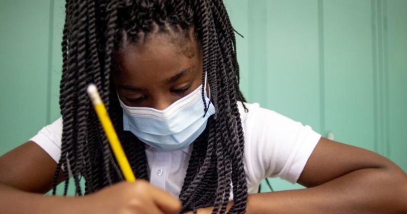 Sixth-grade student Adriana Campbell is seen wearing a mask while writing at Freeman Elementary School in Flint, Michigan in a photo taken on Wednesday.