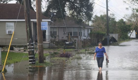 Angelina Coxum walks down a flooded street to check on a relatives home after Hurricane Ida passed through on Aug. 30, in Kenner, Louisiana.