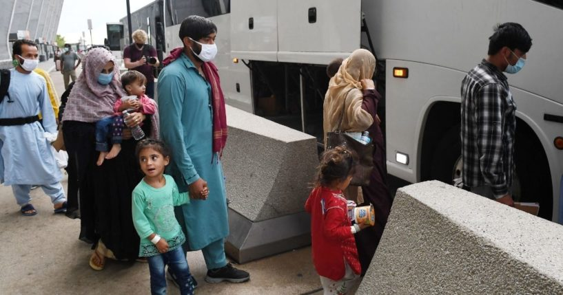 Afghan refugees board a bus after arriving at Dulles International Airport on Aug. 27, in Dulles, Virginia after being evacuated from Kabul following the Taliban takeover of Afghanistan.