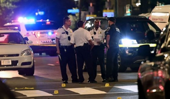 Police officers work at the scene of a shooting outside a restaurant in Washington, D.C., on July 22, 2021.