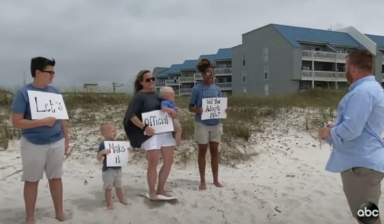 Alecia and her foster family hold up signs asking her foster dad, on his birthday, if he will adopt her.