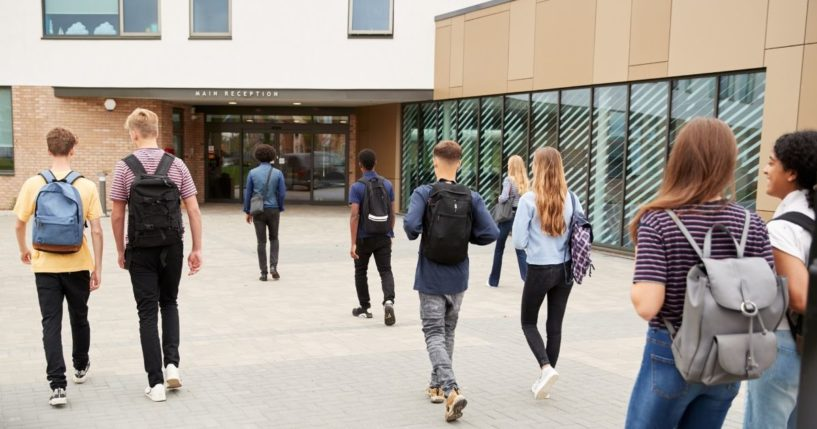 Students are seen walking into a school in the above stock image.