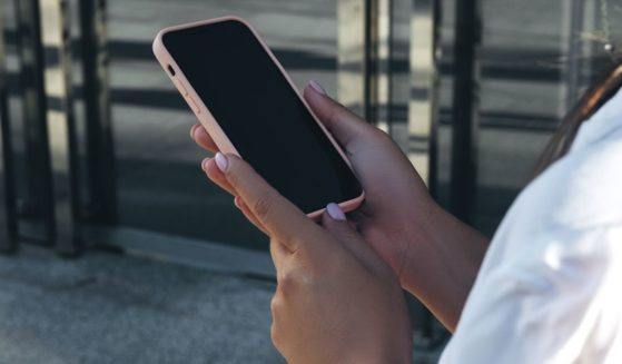 A young woman holds an iPhone 12 Pro.