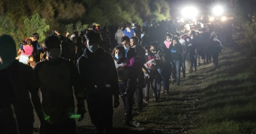Illegal immigrants walk toward transport buses to a processing center on Aug. 14, 2021, in Roma, Texas.