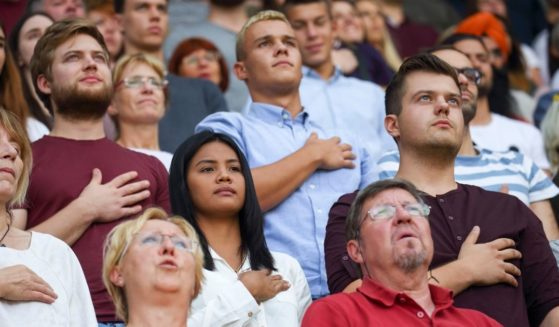 A crowd of people stands for the national anthem in this stock image.