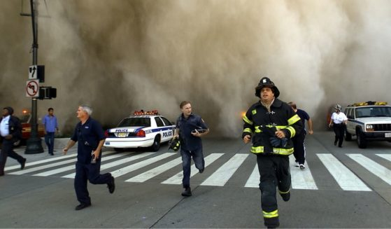 Policemen and firemen run away from a huge dust cloud after terrorists crashed two hijacked airplanes into the twin towers of the World Trade Center on Sept. 11, 2001, in New York City.