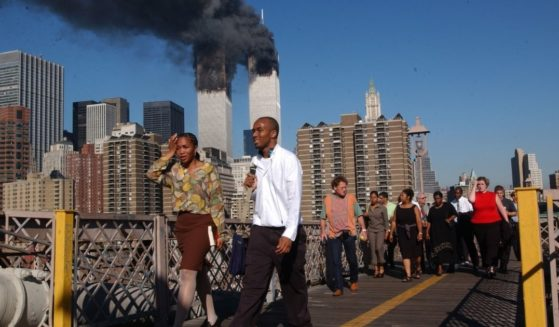 People walk over the Brooklyn Bridge as the World Trade Center burns on Sept. 11, 2001, in New York City.
