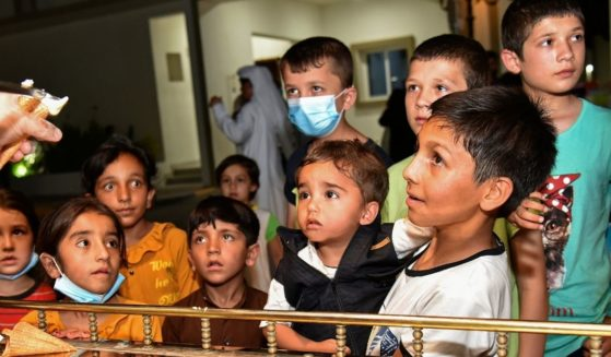 Afghan children who were evacuated from Afghanistan are served ice cream cones