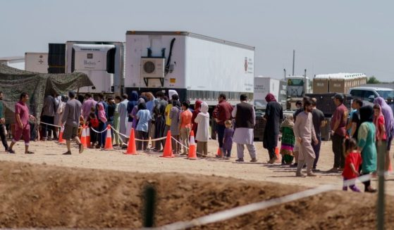 Afghan refugees line up for food outside a dining hall at Fort Bliss' Doña Ana Village, where they are being housed in Chaparral, N.M., on Sept. 10, 2021.