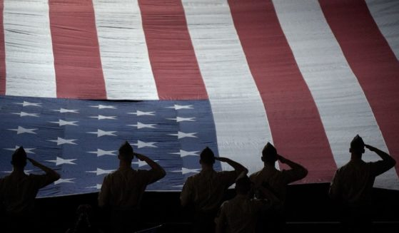American serviceman stand while the national anthem is played during the Salute to Heroes cermony during the BNP Parisbas Open at the Indian Wells Tennis Garden on March 13, 2015, in Indian Wells, California.