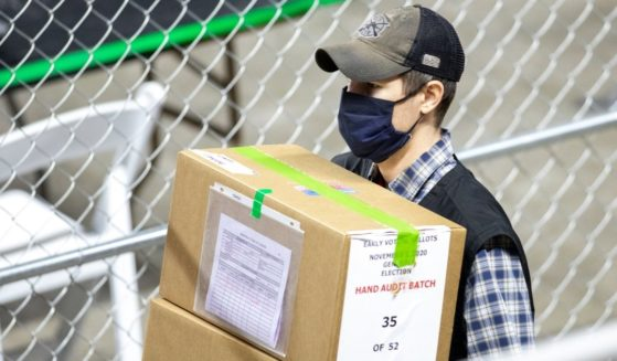 A contractor working for Cyber Ninjas, who was hired by the Arizona State Senate, transports ballots from the 2020 general election at Veterans Memorial Coliseum on May 1, 2021, in Phoenix.