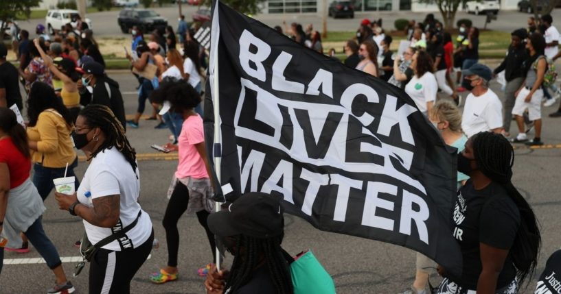 Protesters march with a Black Lives Matter banner on April 29, 2021, in Elizabeth City, North Carolina.