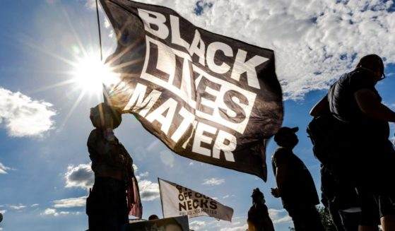 A woman holds a Black Lives Matter flag during a protest outside the Minnesota State Capitol on May 24, 2021 in Saint Paul, Minnesota.