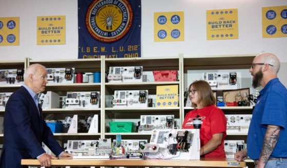 President Joe Biden speaks with instructor Dan McCarthy, right, and apprentice Courtney Groeschen as he tours the International Brotherhood of Electrical Workers training center in Cincinnati, Ohio, on July 21, 2021.