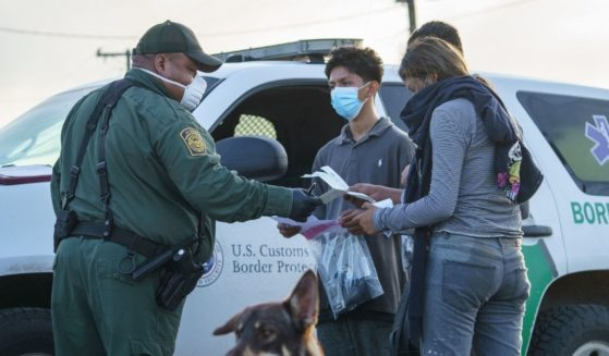 Migrants are processed by a Border Patrol agent after crossing the U.S.-Mexico border in Penitas, Texas, on July 8, 2021.