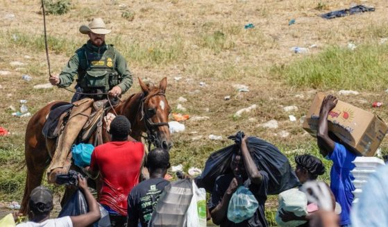 A Border Patrol agent on horseback uses the reins as he tries to stop Haitian migrants from entering an encampment on the banks of the Rio Grande near the Acuna Del Rio International Bridge in Del Rio, Texas, on Sunday.