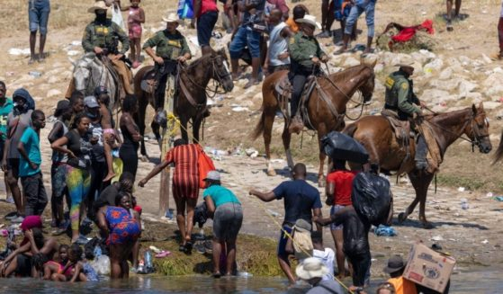 Mounted U.S. Border Patrol agents watch Haitian immigrants on the bank of the Rio Grande in Del Rio, Texas on Monday.