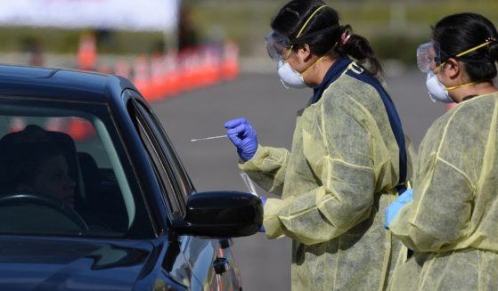 Medical personnel prepare to administer a COVID-19 text at a drive through testing center in California.