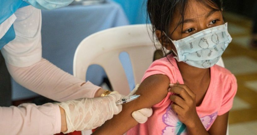A child receives a dose of the Sinovac COVID-19 vaccine at a health center on Saturday in Phnom Penh, Cambodia.