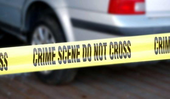 Yellow tape blocks off a crime scene involving a car.