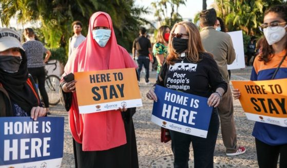 People hold signs during a rally in support of the Obama administration's Deferred Action for Childhood Arrivals program in San Diego on June 18, 2020.