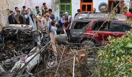 Afghan residents and family members of the reported victims gather next to a damaged vehicle outside a house, after a U.S. drone airstrike in Kabul allegedly killed 10 people on Aug. 30, 2021.